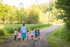 Image of one adult and seven children walking down a dirt road in a country setting.