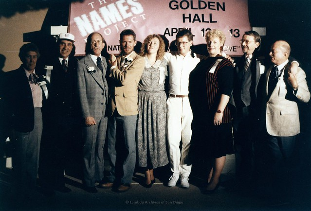 "Cleve Jones (in white) and the San Diego Names Project Committee."" from left: Barbara Crusberg, Pat Rocco, Jess Jessop, Albert Bell, Unknown, Cleve Jones, Susan Jester, unknown, Herb King"