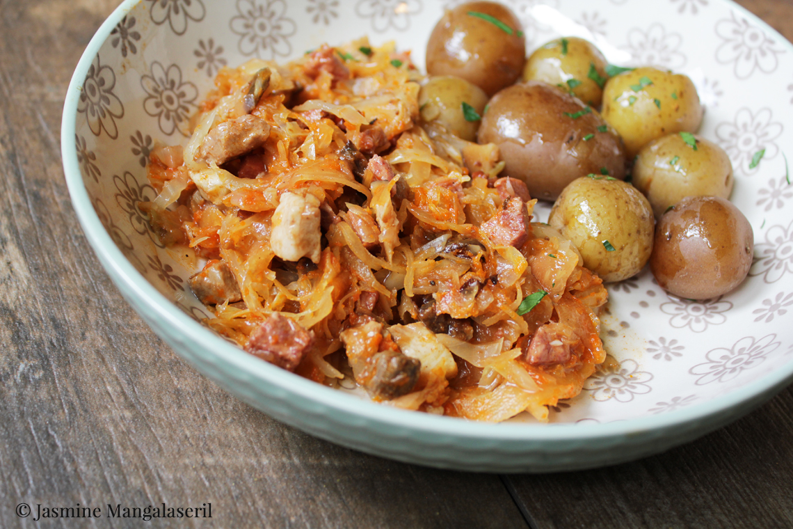 A dish of bigos with boiled baby potatoes