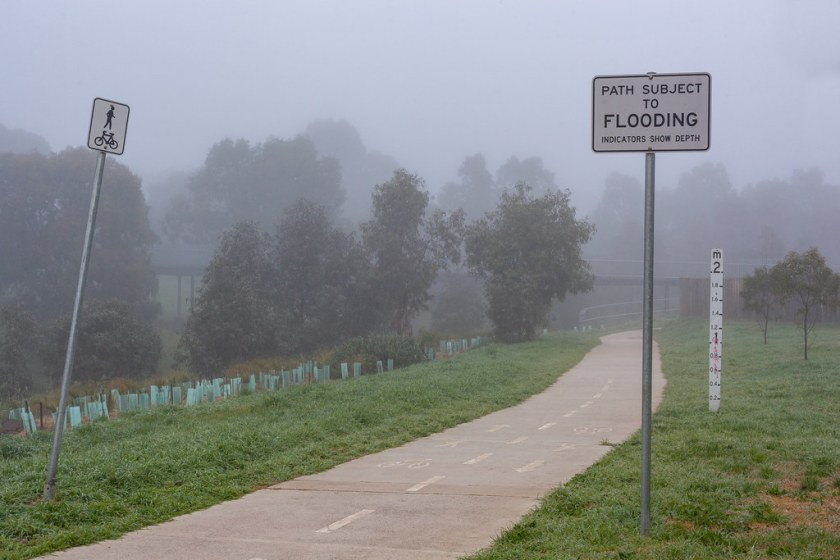 A fog shrouded bike path with signs indicating flooding
