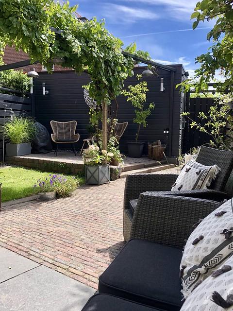 Zwarte tuin met verhoging rotan vlinder tuinstoelen