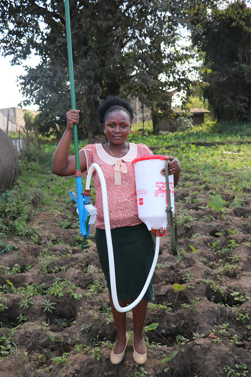 Lilian Richard, an Africa RISING innovator student from Tanzania holding her patented innovation - the soil dose fertilizer applicator is used. Photo credit: Eveline Massam/IITA.