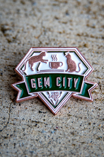 "A pin with two cats in it, and the legend ""Gem City Catfe,"" and all done in a gem shape."