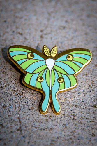 A pin of a blue and green luna moth.