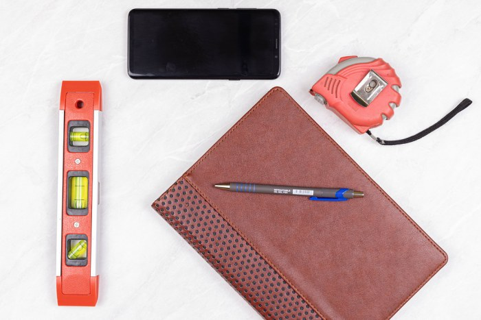 Top view Level Measure Tape Mobile phone Pencil and Paper Notebook