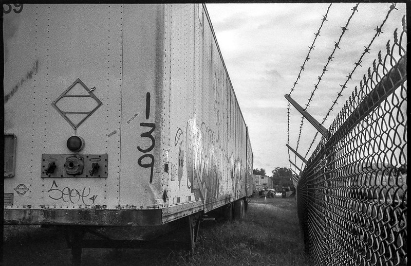 abandoned tractor trailor, metal fence, barbed wire, Asheville Waste Paper Company, Asheville, NC, Leica C1, Fomapan 200, Moersch Eco film developer, late August 2020 (1 of 1)