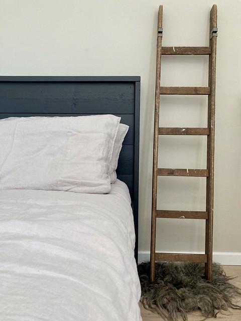 Oude ladder naast het bed linnen beddengoed