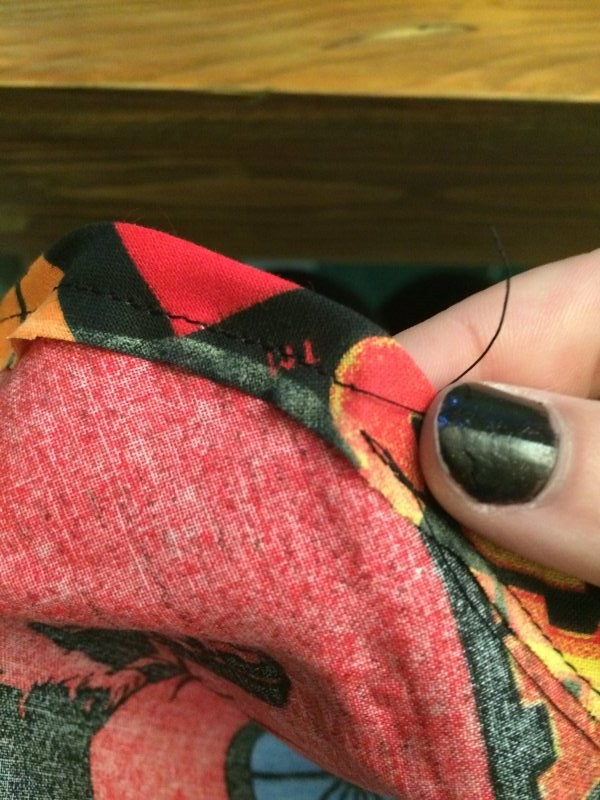 Fold over the edge and stitch! Leave a small opening so you can thread the string back through.