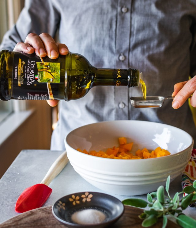tossing the squash with a drizzle of extra virgin olive oil