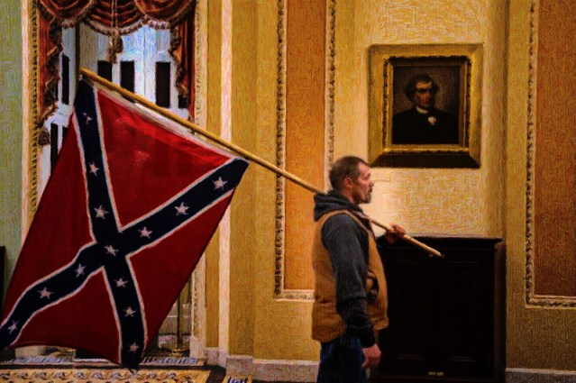 One of the invaders of the Capitol, wandering around with a Confederate flag.