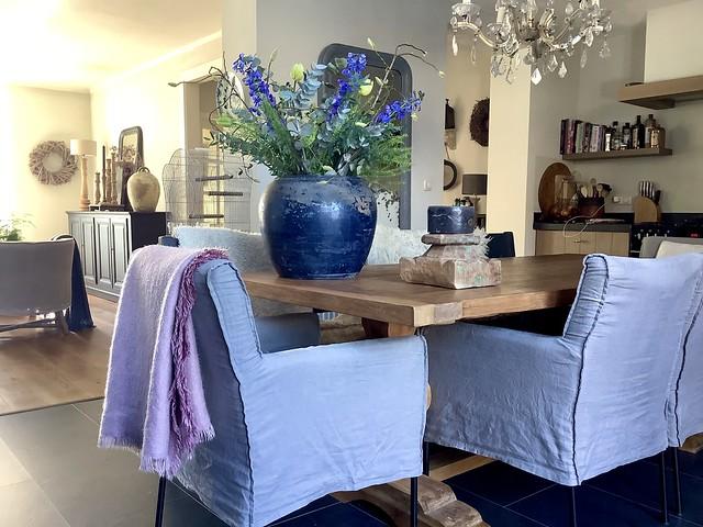 Grote blauwe pot met bloemen stoel linnen hoes plaid poer