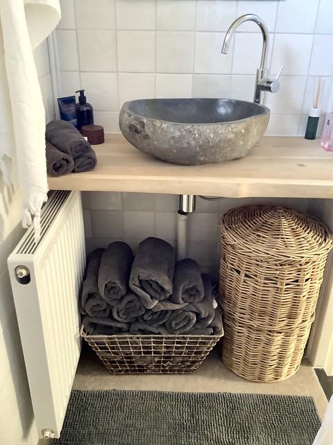Stenen waskom opgerolde handdoeken in draadmand rotan wasmand met deksel