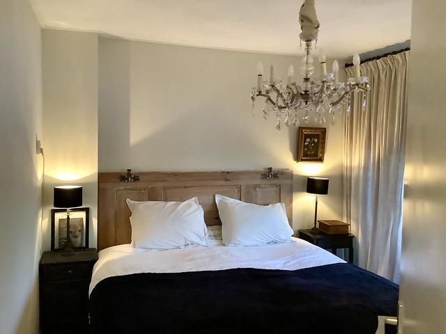 Houten bed kroonluchter met stof natuurtinten slaapkamer