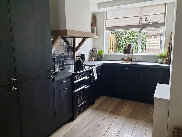 Zwarte landelijke keuken grijs blad houten schouw
