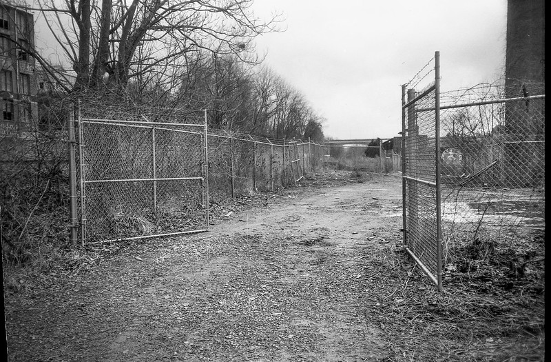 open gates, barbed wire, fence, driveway, urban decay, River District, Asheville, NC, Nikon L35AF2 (One Touch), Arista.Edu 200, Ilfosol 3 developer, Early May, 2021