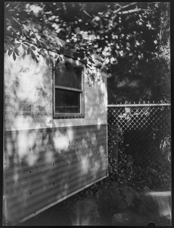shed, deep shadows, metal fence, yard, Asheville, NC, Fotokor 1, VOOMP Anastigmat Ortagoz 135mm f-4.5, Fomapan 100, Ilfosol 3 developer, 6.15.21