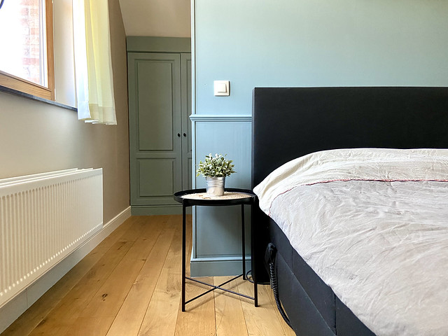 Blauwe muur landelijke slaapkamer zwart bed zwart nachttafeltje
