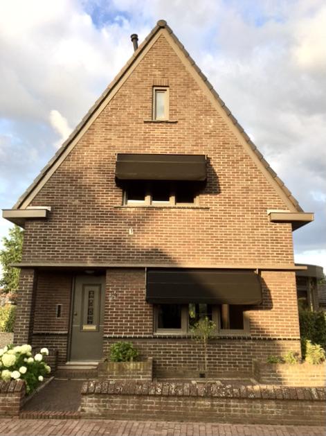 Voorgevel jaren '30 huis taupe kozijnen grijsgroene voordeur