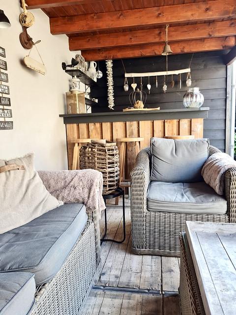 Houten bar onder overkapping steenschot vloer loungeset