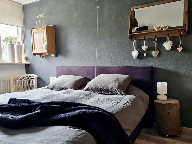 Grijze muur slaapkamer kapstok boven het bed boomstam met IKEA bedlampje