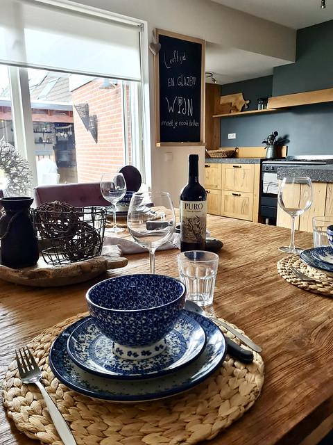 landelijk gedekte tafel met rotan placemat en blauw servies