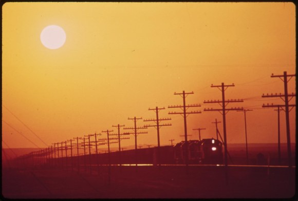Transmission lines and railroad near Salton Sea. District of Los Angeles smog obscures the sun, May 1972