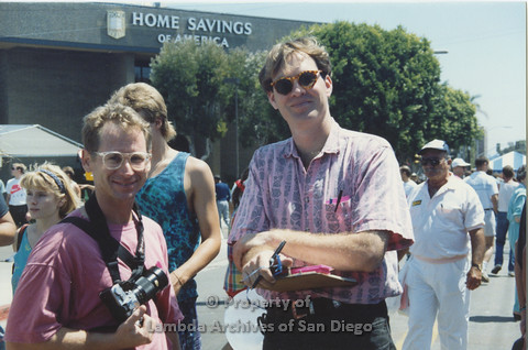 P001.108m.r.t 2 people, man on the left is holding a camera and the man on the right is holding a clipboard