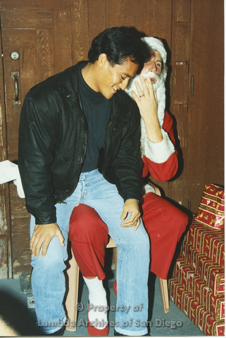 P001.273m.r.t X-mas: man in black jacket sitting on Santa's lap