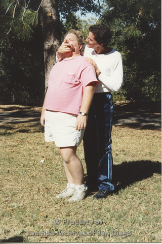 P001.191m.r.t Retreat 1991: man in blue stripped pants covering the mouth of a man in pink t-shirt
