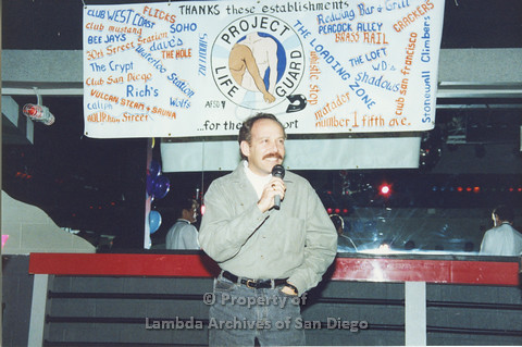 P001.317m.r.t Date Auction: man in green shirt onstage holding a microphone