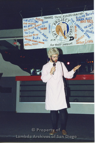 P001.324m.r.t Date Auction: man in drag wearing a pink dress holding a microphone