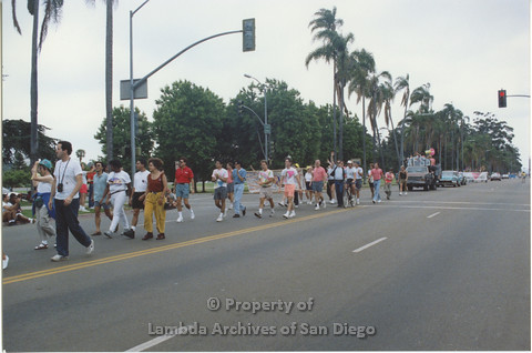 P001.053m.r Pride 1991: People walking in the Pride Parade in front of the AIDS Foundation San Diego Parade Float