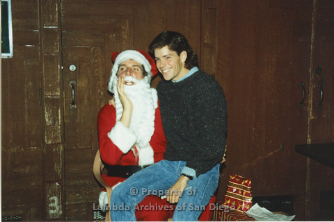 P001.302m.r.t X-mas: man in black sweater and jeans sitting on Santa's lap