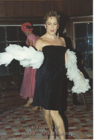 P001.219m.r.t Retreat 1991: man in drag wearing a black dress and a white boa, another man in drag wearing a pink dress in the background
