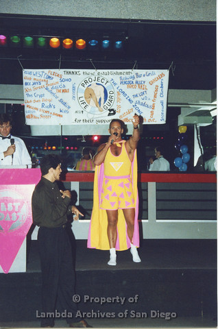 "P001.315m.r.t Date Auction: man in""Safer Sex Dude"" costume onstage holding a microphone"