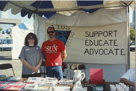 P001.123m.r.t AIDS Walk 1991: AIDS Foundation San Diego Booth with a banner (AIDS Foundation San Diego: Support, Educate, Advocate) 2 volunteers in booth
