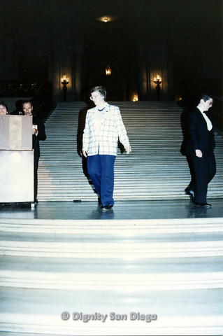 P103.115m.r.t Dignity Ninth Biennial Convention 1989: Person with plaid suit jacket and person with tuxedo walking down stairs