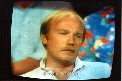 P103.071m.r.t Dignity San Diego:  Photo of a blond man during televised AIDS program
