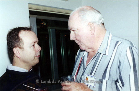 P040.038m.r.t SAGE General Meeting; two men talking, one with nametag (Joe F.)