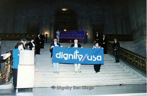 "P103.114m.r.t Dignity Ninth Biennial Convention 1989: Men and women walking down stairs holding signs Dignity/ USA"" and ""Dignity: We're here for GOOD! Lesbian and Gay Catholics"""