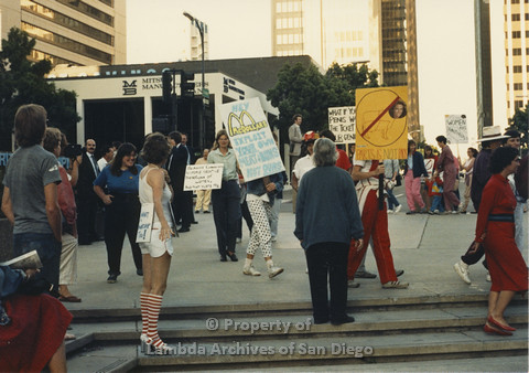 P024.108m.r.t Myth California Protest, San Diego, June 1986: candid shot of marchers one at the center in polka-dot pants holding a sign (Hey McDollars Exploit your own Meat & Buns Not Ours)