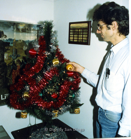"P103.198m.r.t A man hanging a decoration on a Christmas tree.  Plaque on back says ""Dignity San Diego: [Outstanding] Service Award"""