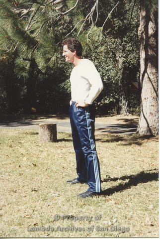 P001.190m.r.t Retreat 1991: man standing outside in blue stripped pants