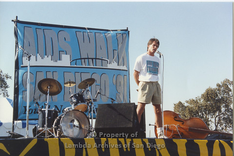 P001.119m.r.t Aids Walk 1991: Man speaking into microphone on stage
