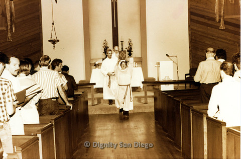 P103.054m.r.t Dignity San Diego: Clergy person holding up book in middle of church isle