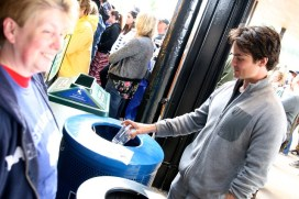 A man throwing a plastic bottle into the blue bin for recycling