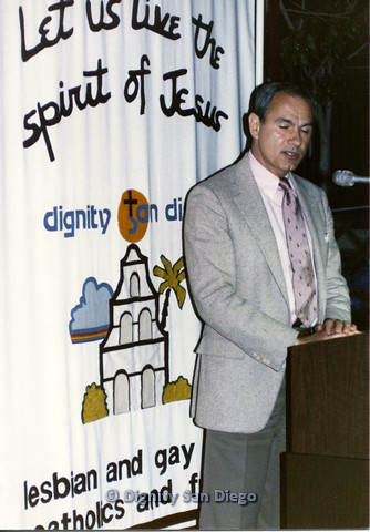 P103.204m.r.t Man in grey suit jacket talking on podium in front of Dignity San Diego banner