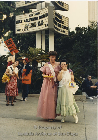 P024.111m.r.t Myth California Protest, San Diego, June 1986: two girls wearing sashes (from left to right: Miss Represented, Miss Quarter Pounder) standing in front of the Civic Theatre Marquee