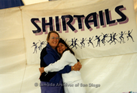 San Diego LGBT Pride Festival, July 1999: Lesbian Couple Sheila Clark (left) hugging Judy Reif (right) in front of Shirtails Dances Banner
