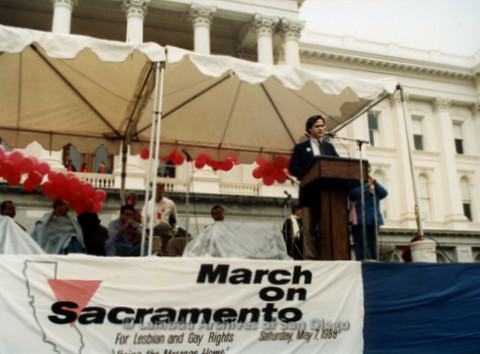 P019.100m.r.t March on Sacramento 1988 / Pre Parade gathering: Man on stage speaking in front of city hall.